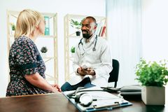 Una donna senior che visita un terapista alla clinica fotografia stock libera da diritti