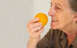 Una donna senior con un'arancia Fotografia Stock