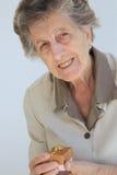 Una donna senior con un presente Fotografia Stock