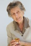 Una donna senior con un presente Immagini Stock Libere da Diritti