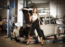 Una donna sexy che ripara un'automobile in un garage fotografie stock