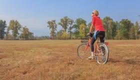 Una donna si esercita su una bicicletta Immagine Stock