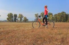 Una donna si esercita su una bicicletta Fotografia Stock