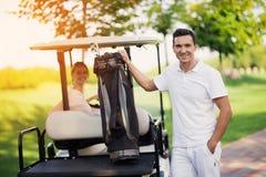 Una donna si siede dietro la ruota di un carretto di golf, i supporti di un uomo nella priorità alta e le tenute una borsa con i  Fotografie Stock Libere da Diritti