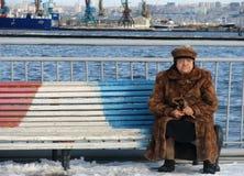 Una donna si siede in una pelliccia su un pilastro nel porto di Bacu - l'AZERBAIGIAN Immagine Stock Libera da Diritti