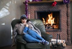 Una donna si siede in una sedia vicino ad un camino bruciante Fotografie Stock Libere da Diritti