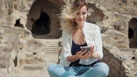 Una donna si siede su una pietra e controlla la posta sul telefono che le free lance lavorano da ogni angolo del mondo stock footage