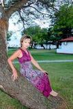 Una donna si siede in un albero Immagini Stock Libere da Diritti