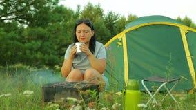 Una donna si siede vicino ad una tenda, beve il tè e cucina la carne sulla griglia stock footage