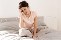 Una donna sola sta gridando da solo, la sua mascara ha scorso Si siede su un letto in una stanza luminosa Immagini Stock Libere da Diritti