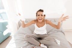 Una donna sola sta gridando da solo, la sua mascara ha scorso Si siede su un letto in una stanza luminosa Fotografia Stock