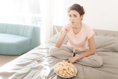 Una donna sola sta gridando da solo, la sua mascara ha scorso Si siede su un letto in una stanza luminosa Fotografia Stock Libera da Diritti