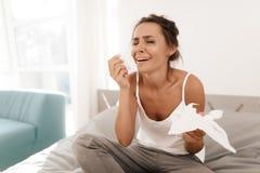 Una donna sola sta gridando da solo, la sua mascara ha scorso Si siede su un letto in una stanza luminosa Immagine Stock