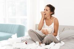 Una donna sola sta gridando da solo, la sua mascara ha scorso Si siede su un letto in una stanza luminosa Fotografie Stock