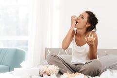 Una donna sola sta gridando da solo, la sua mascara ha scorso Si siede su un letto in una stanza luminosa Immagine Stock Libera da Diritti