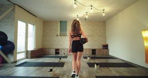 In una donna soleggiata dello studio di yoga che entra in studio con la sua propria stuoia di sport per iniziare la meditazione d archivi video