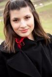 Una donna sorridente con un cappotto immagini stock libere da diritti