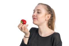 Una donna sorridente gode di di mangiare una fragola fotografia stock libera da diritti