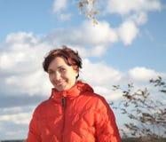 Una donna sorridente in rivestimento rosso Fotografie Stock