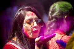 Una donna spalmata di polvere colorata, partecipa alle celebrazioni del festival di Dol Utsav Immagini Stock