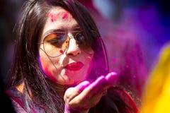 Una donna spalmata di polvere colorata, partecipa alle celebrazioni del festival di Dol Utsav Immagine Stock
