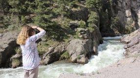 Una donna spara le foto sulla strada secondaria remota del ciclo alpino Fotografie Stock Libere da Diritti