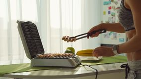 Una donna sportiva che cucina le cialde belghe deliziose del mirtillo per la prima colazione di mattina nella cucina video d archivio