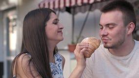 Una donna sta alimentando al suo ragazzo un croissant al caffè archivi video