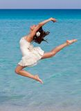Una donna sta ballando sulla spiaggia Fotografie Stock
