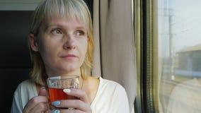 Una donna sta bevendo il tè sul treno Viaggiando con la comodità video d archivio
