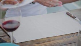 Una donna sta cambiando i piatti da pizza alle ali di pollo fritto archivi video