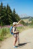 Una donna sta camminando in montagne Immagini Stock