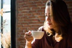 Una donna sta comperando su Internet mentre metteva il poco sorriso sul suo fronte fotografia stock