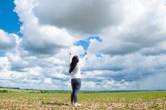Una donna sta con le sue armi alzate e prega a Dio Su un campo verde di estate fotografia stock