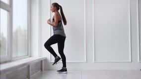 Una donna sta facendo gli esercizi attivi per rinforzare i muscoli delle gambe e delle natiche stock footage