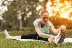Una donna sta facendo l'allungamento su una coperta per yoga nel parco Si trascina ai suoi piedi Immagine Stock Libera da Diritti