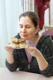 Una donna sta inalando il sapore di nuovi dolci al forno Fotografie Stock