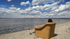 Una donna sta mettendo sulla poltrona e sta vedendo su un lago immagini stock