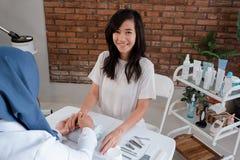 Una donna sta ottenendo una comodità della lozione per le mani molto con l'estetista fotografie stock