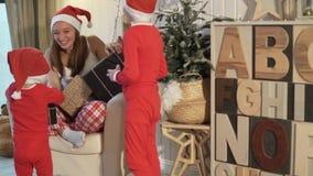Una donna sta sedendosi in una sedia in pigiami di Natale video d archivio