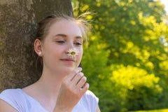 Una donna sta sedendosi sotto un albero ed odora su un fiore fotografie stock