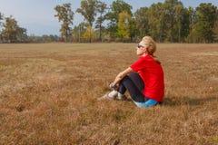 Una donna sta sedendosi in un parco e sta ammirando il paesaggio Immagine Stock Libera da Diritti