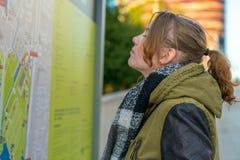 Una donna sta stando davanti ad una mappa che cerca il suo obiettivo fotografia stock