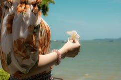 Una donna sta stando vicino al mare fotografia stock