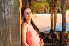 Una donna sta sulla spiaggia nella sera La ragazza al tramonto Giovane signora attraente che gode di ultimi raggi del sole immagini stock