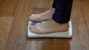 Una donna sta sulle scale ed impara il suo peso, primo piano archivi video