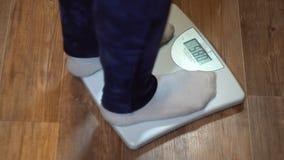 Una donna sta sulle scale ed impara il suo peso, primo piano stock footage