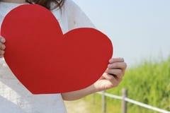 Una donna sta tenendo un cuore rosso di carta Fotografia Stock Libera da Diritti