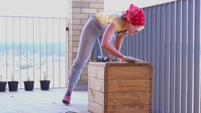 Una donna su un terrazzo fa un lavoro non femminile - perfora un pozzo con un cacciavite in una scatola di legno archivi video