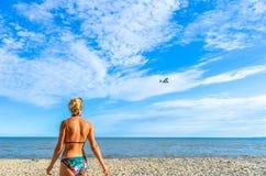 Una donna sulla spiaggia guarda un piccolo piano volare vicino Immagine Stock